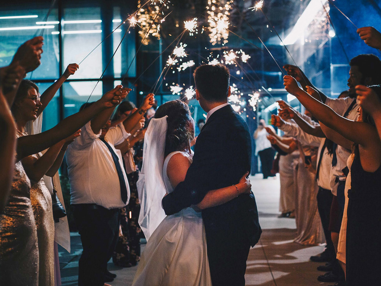A newly married couple embraces and looks at a tunnel of sparklers held aloft by wedding guests