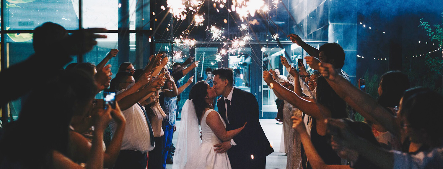A newly married couple kisses under a tunnel of sparklers held by wedding guests