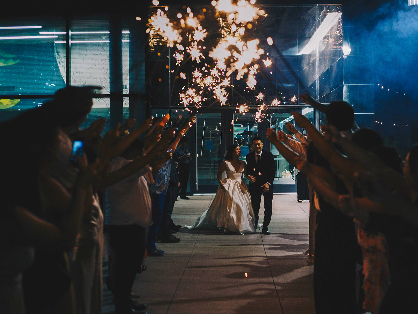 A newly married couple prepares to go through a tunnel of sparklers held up by wedding guests