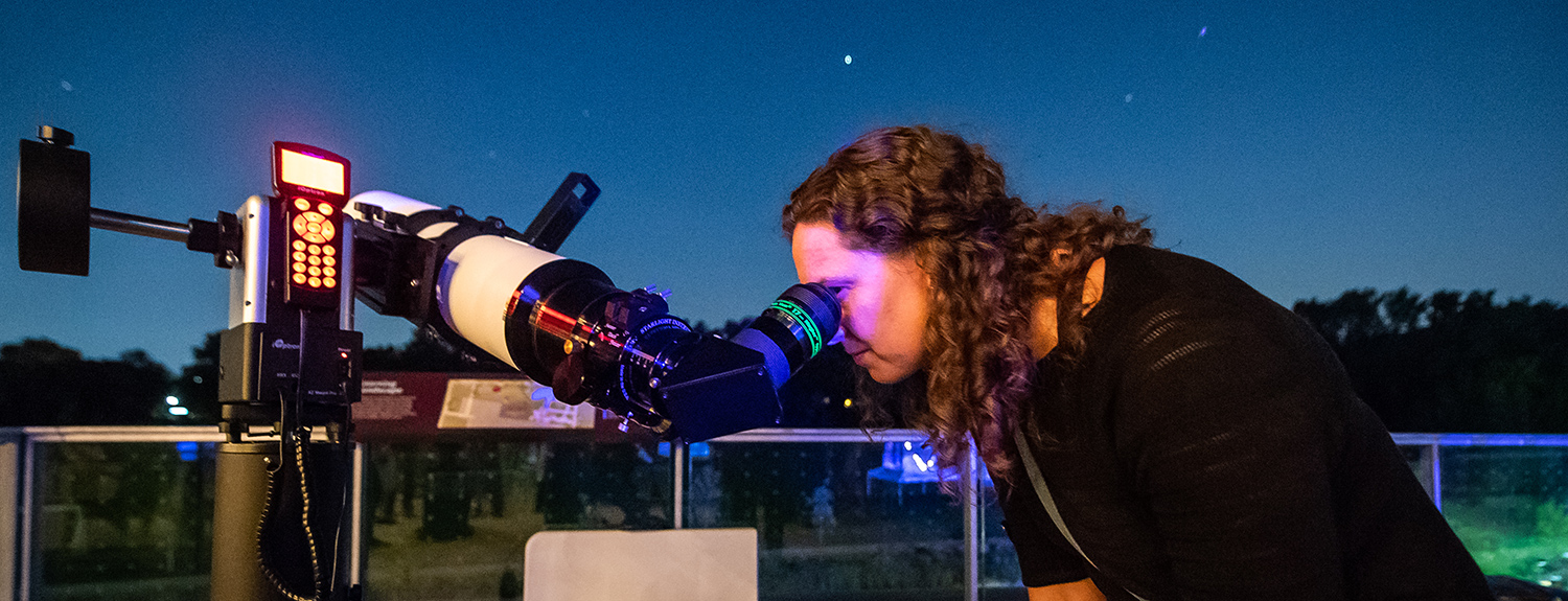 A woman looks at the night sky through a large telescope