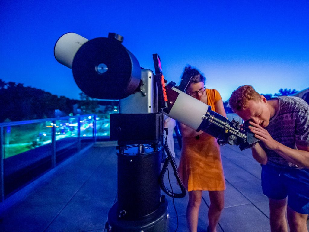 Visitors look through a high-powered telescope on the museum's outdoor observation deck