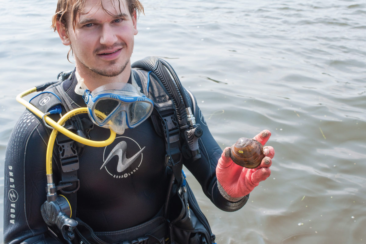 Student in a wetsuit and diving gear holding a live mussel.