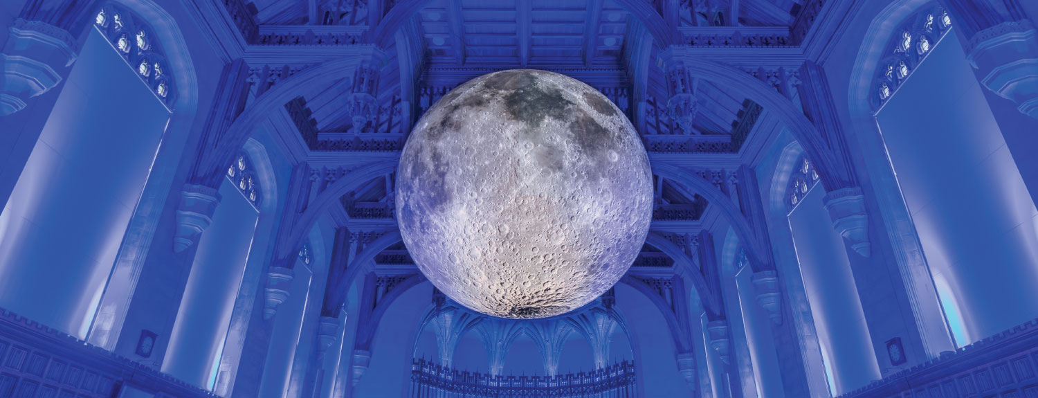 Museum of the Moon suspended high above a blue-lit room at the University of Bristol.