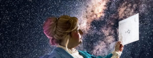 Photo of actor playing Henrietta Leavitt in front of a starry sky, examining a paper