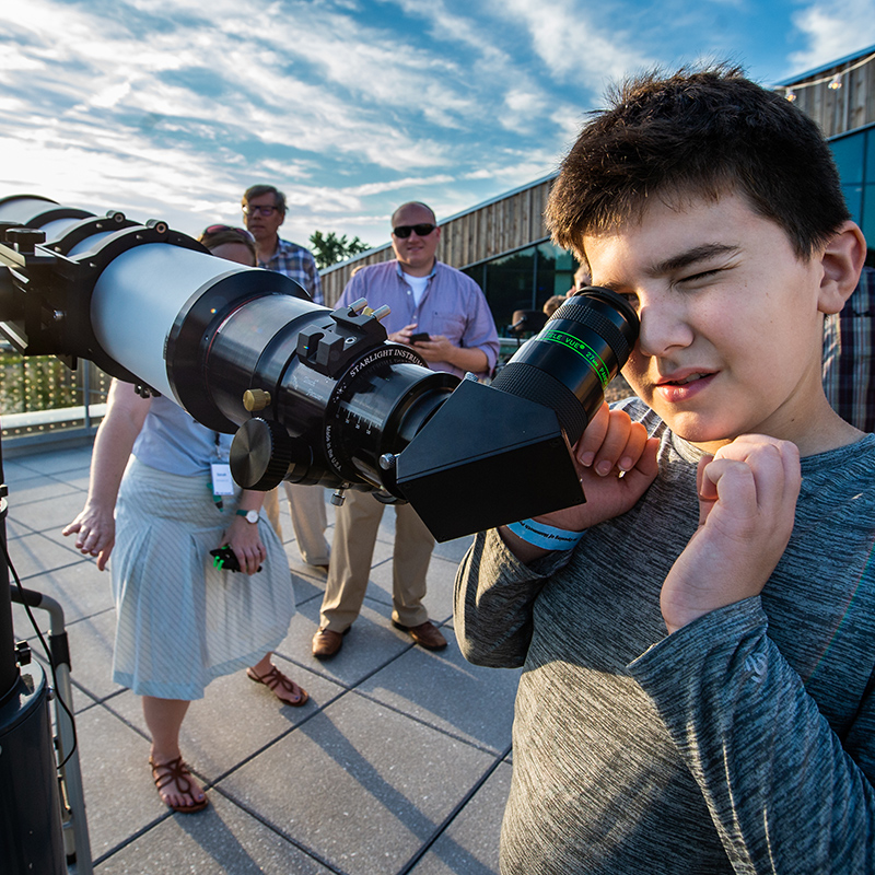 A boy looks through a telescope on the Bell Museum's observation deck