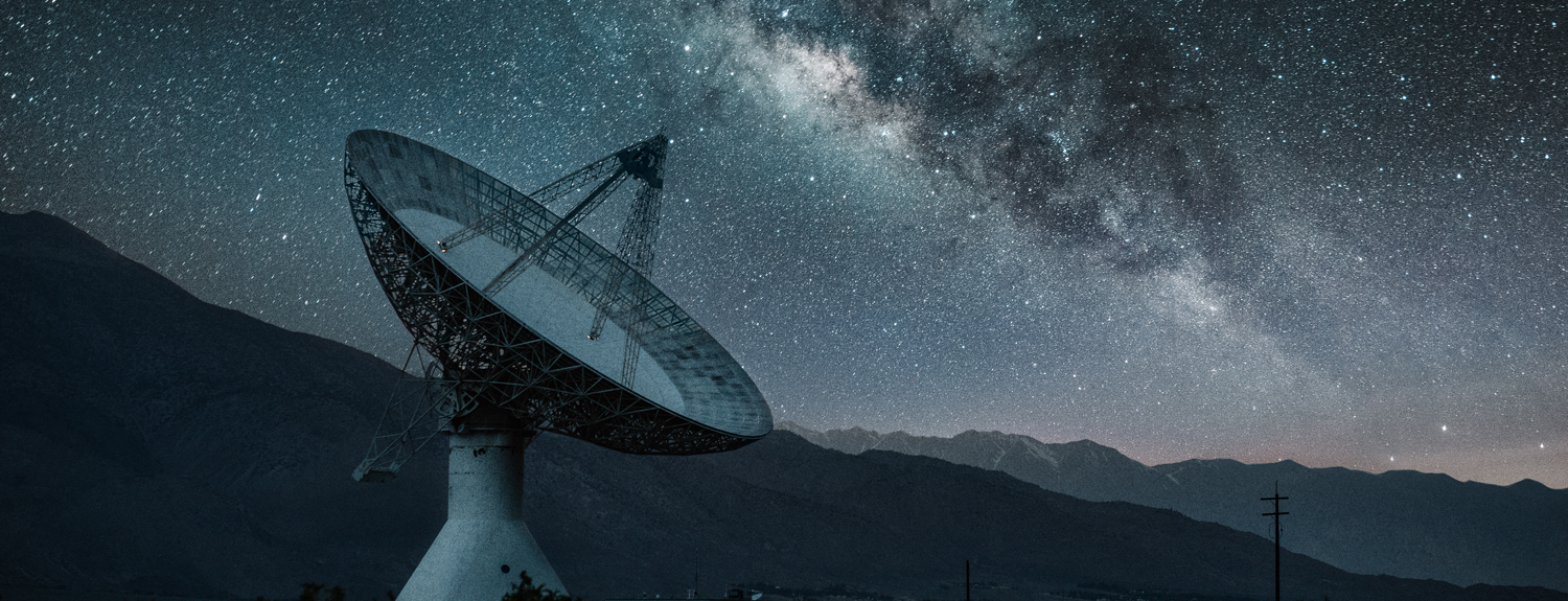 A radio telescope in front of starry skies