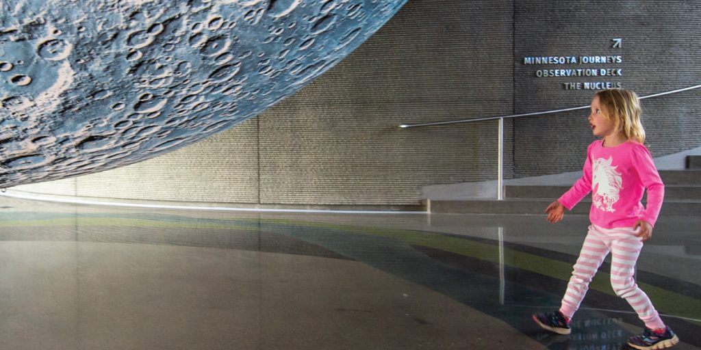 Young girl approaches Museum of the Moon installation