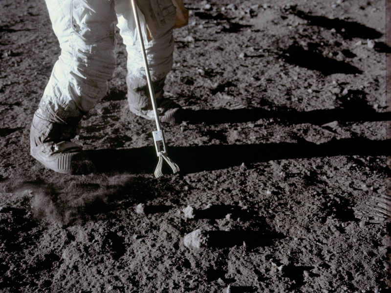 An Apollo astronaut takes a lunar sample