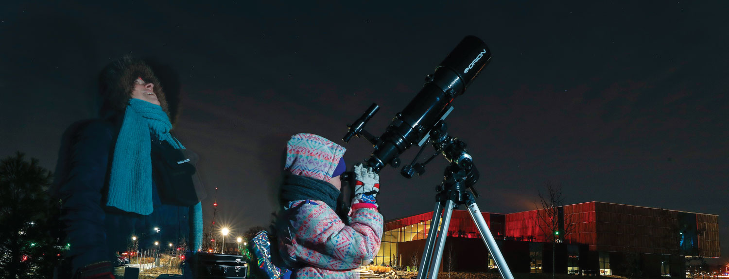 Family stargazing outside with a telescope