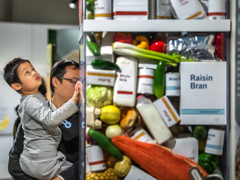 Visitors looking at a food waste Tower in the Global Kitchen exhibit