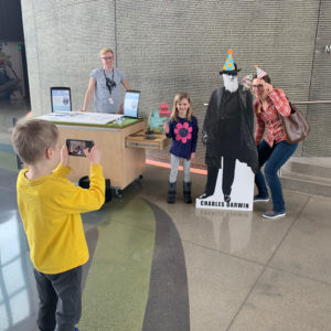 A young visitor takes a photo of his family posing with a cardboard cutout of Darwin