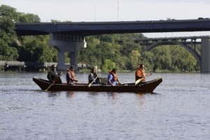team using Micronesian outrigger canoe in a Minnesota river