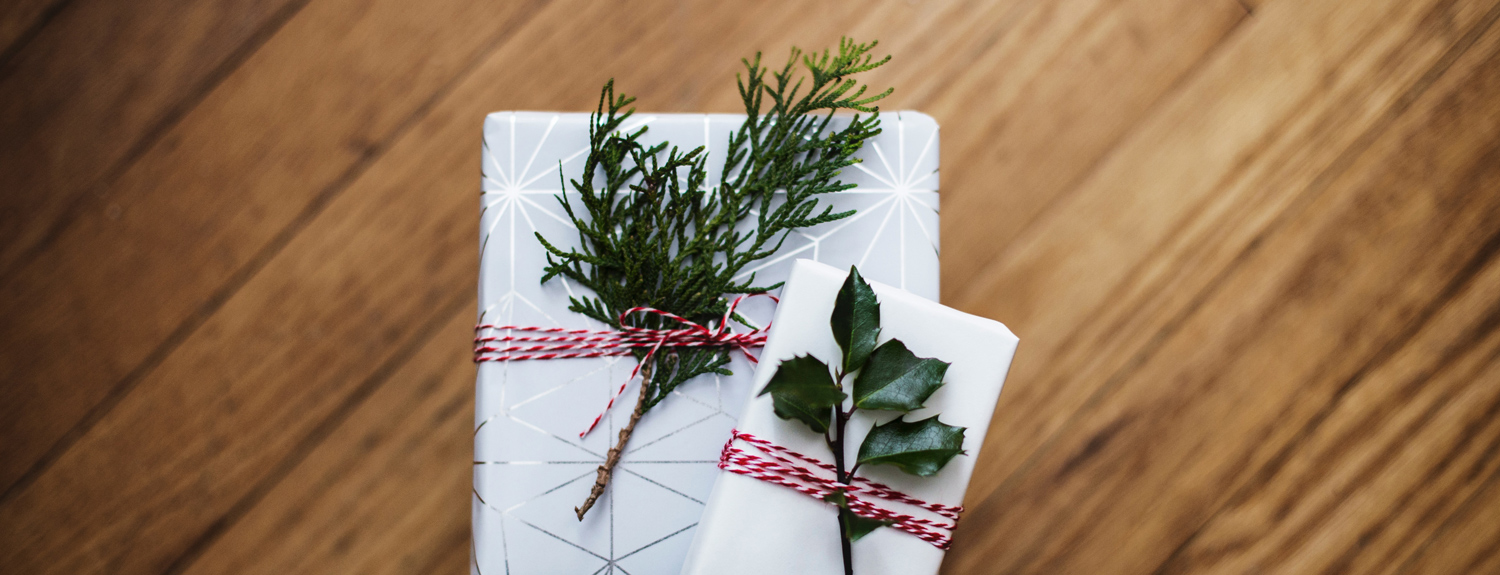 White-wrapped gifts with sprigs of greenery on a wooden table