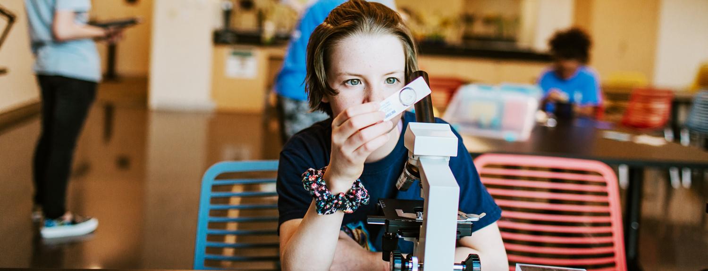 A camper examining a microscope slide