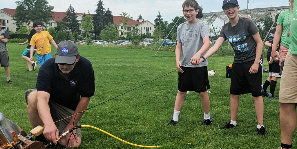 Summer campers get ready to launch rockets on the field near the museum
