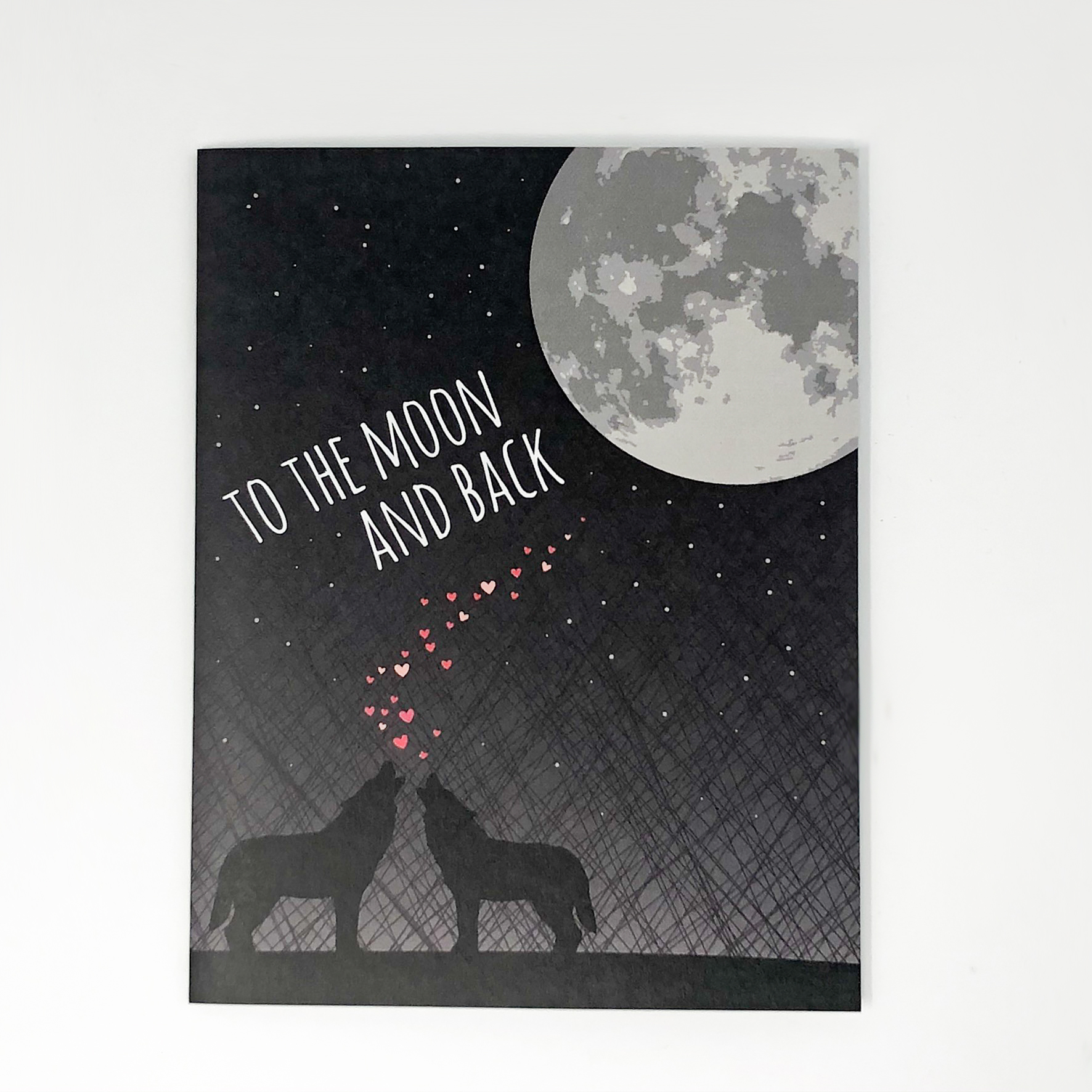 A greeting card with wolves and the moon, saying,