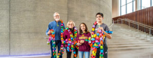A family holds a paper chain with the digits of pi