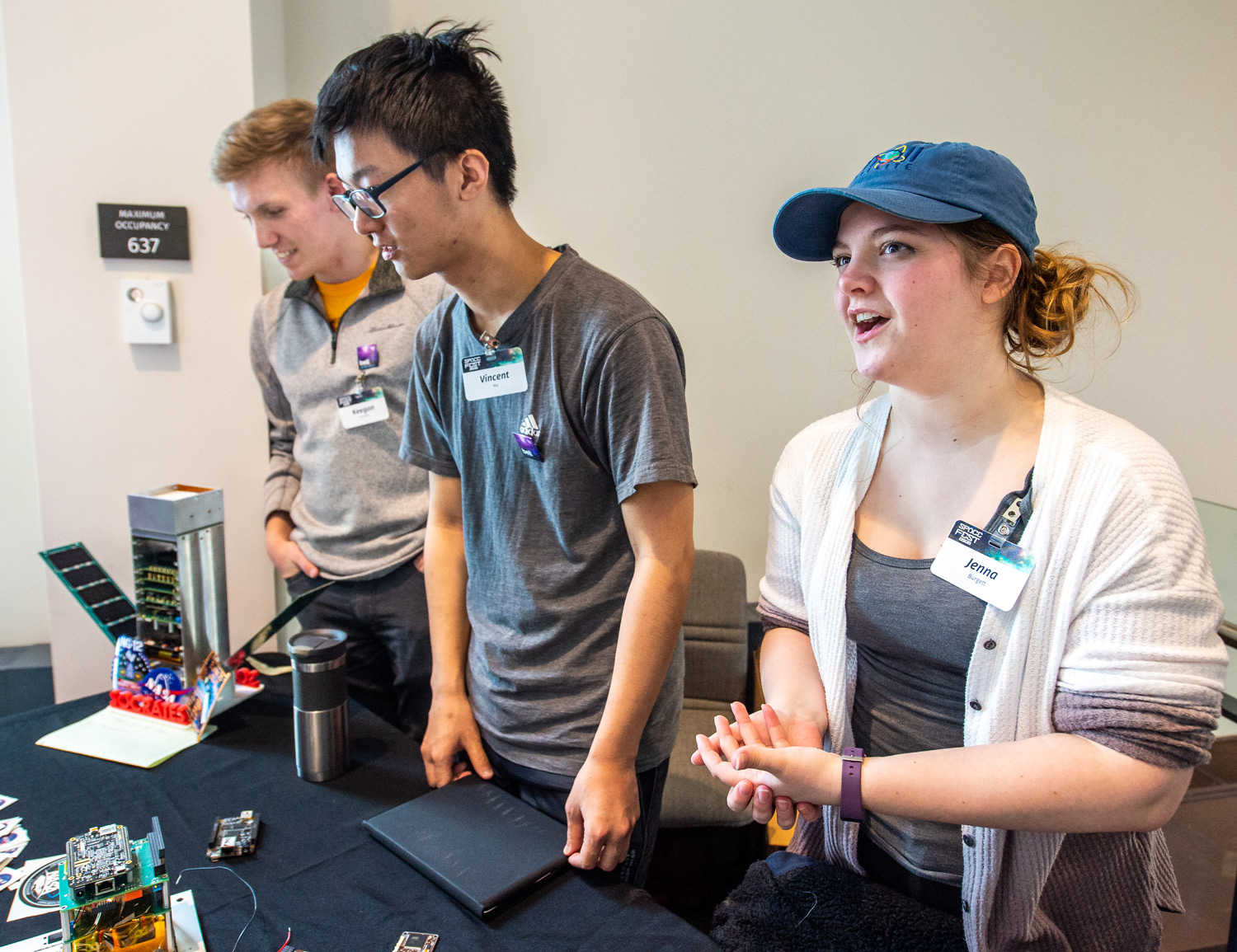 Students from the U of M show visitors components from a CubeSat