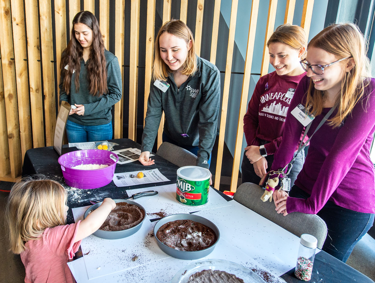 U of M students demonstrate to young visitor how craters form on the moon