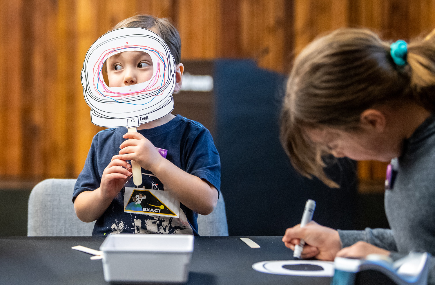 Young visitor shows off their astronaut mask