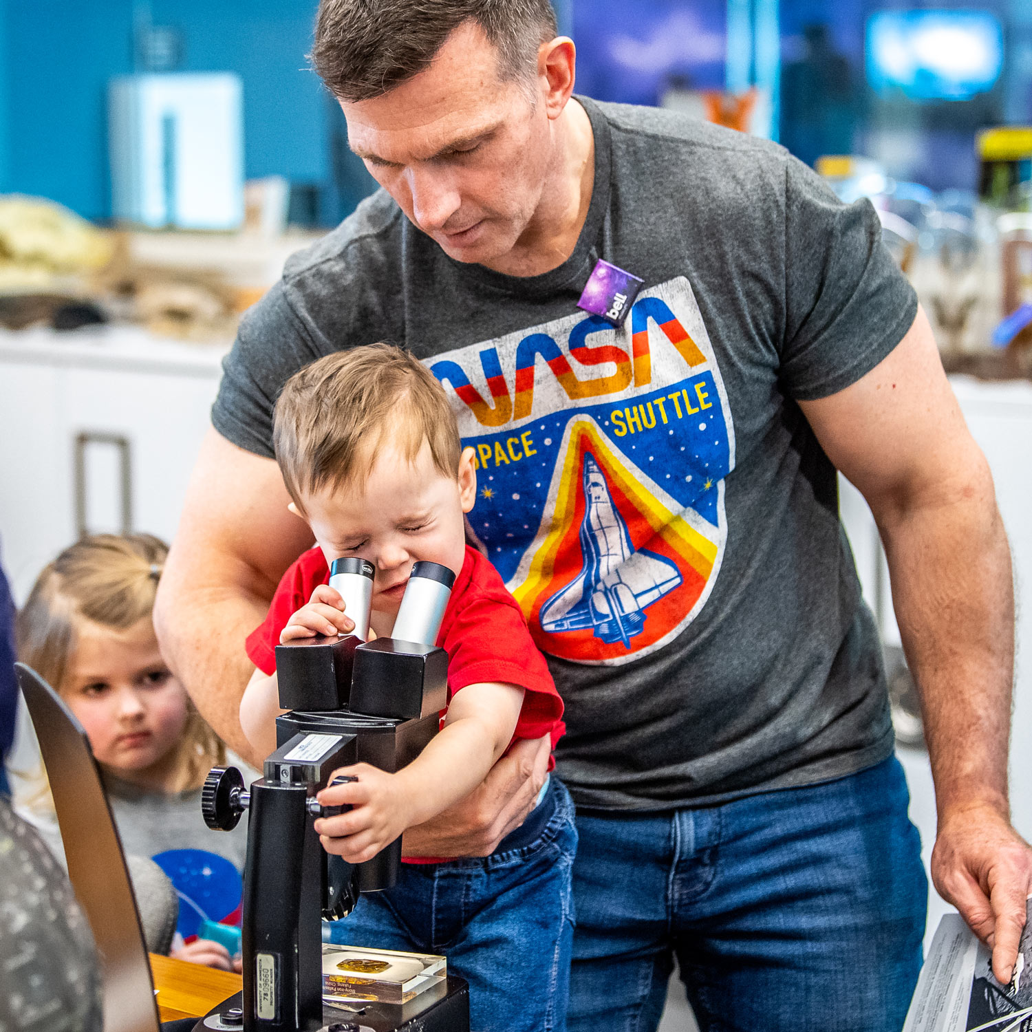 Young visitor looks through microscope and examines meteorite