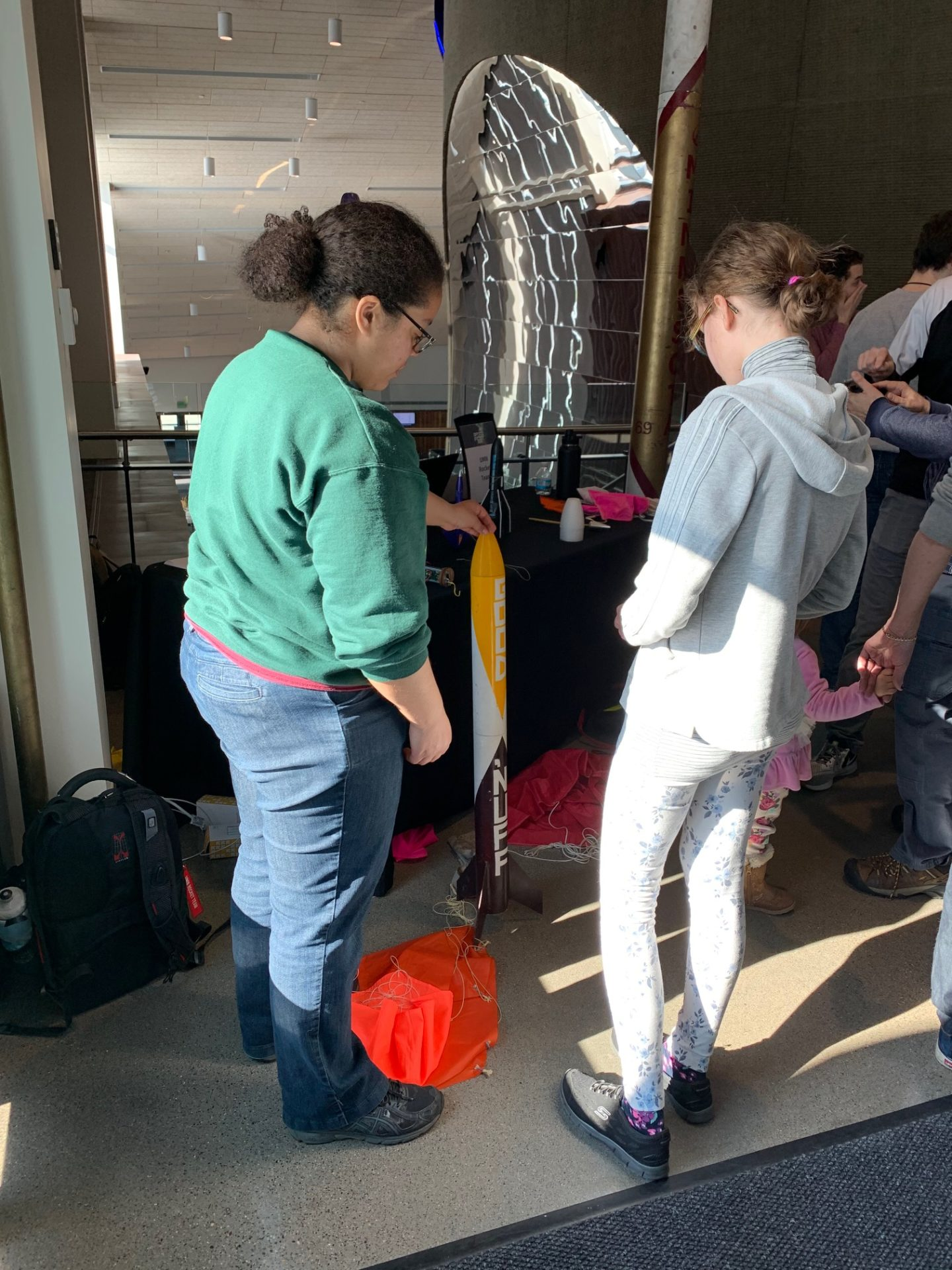 U of M student demonstrates rocket features to visitor