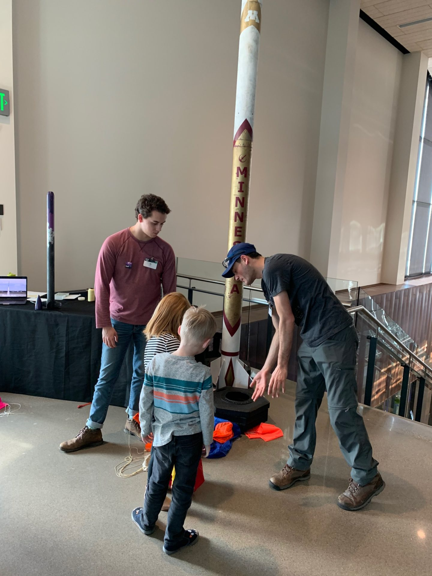 U of M students explain rocket features to young visitors