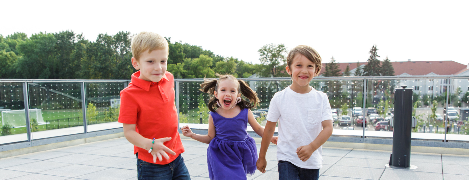 Three kids looking happy and excited outside in the summer