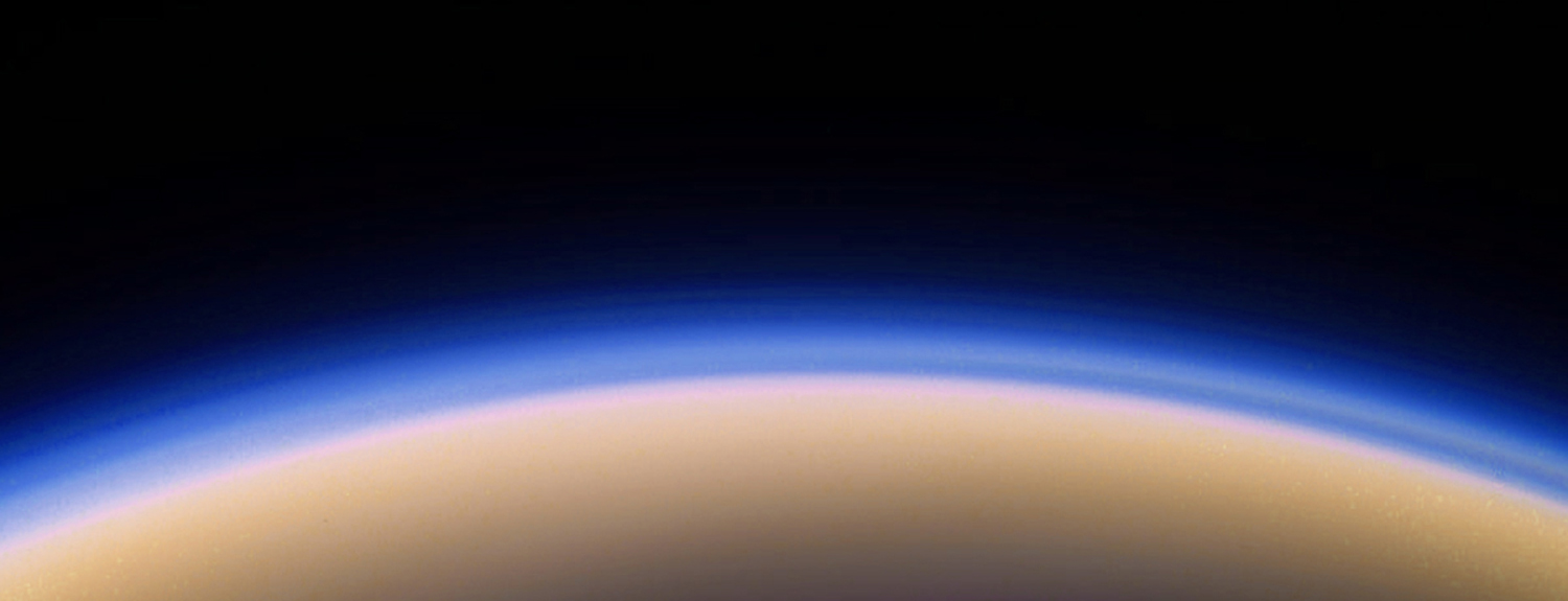 Telescope image of Titan (moon of Saturn), a hazy arch of blue over white
