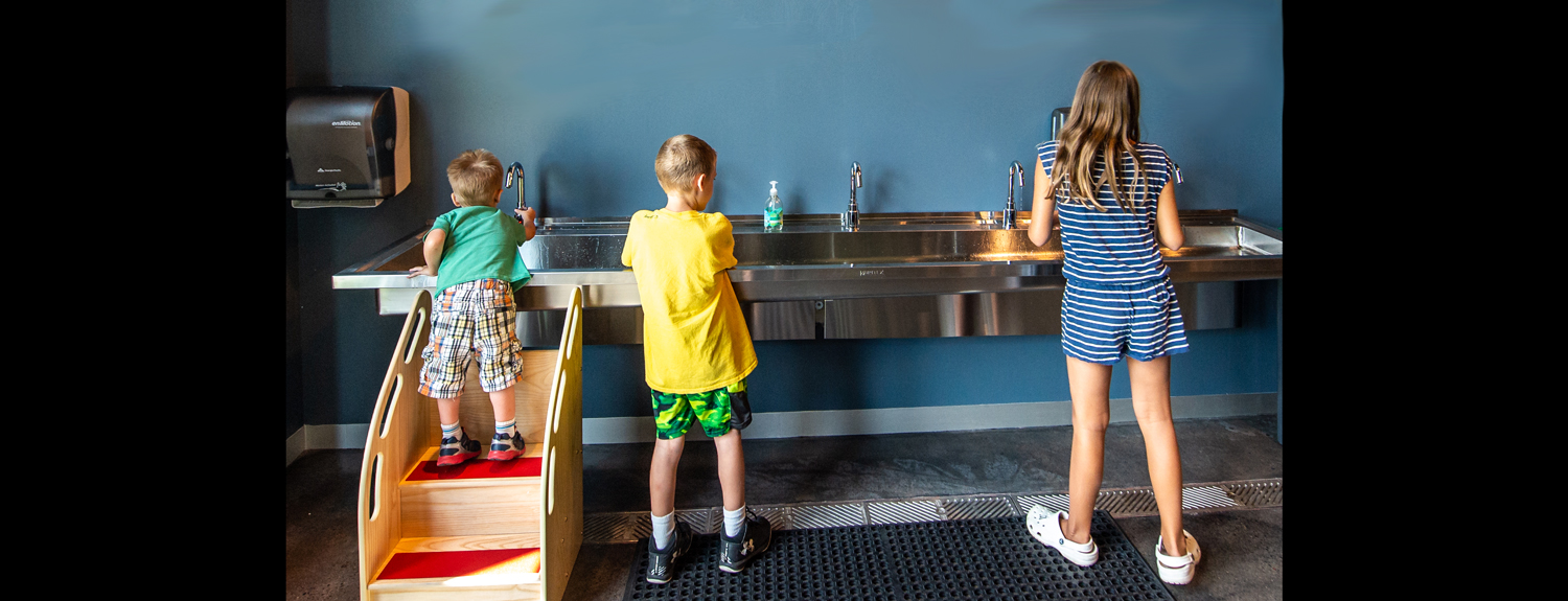 Three kids washing their hands at a long sink