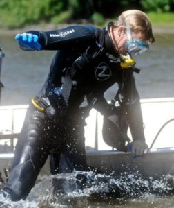 Student in wet suit jumps out of a boat
