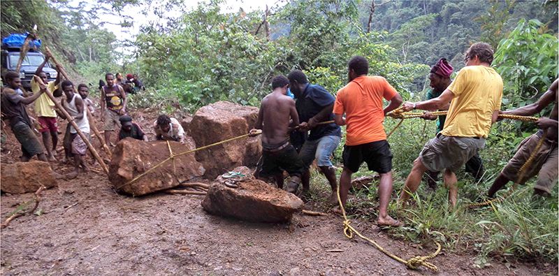 A group of men use sticks and rope to clear boulders from a road