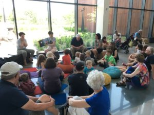 student volunteers reading to a group of museum guests