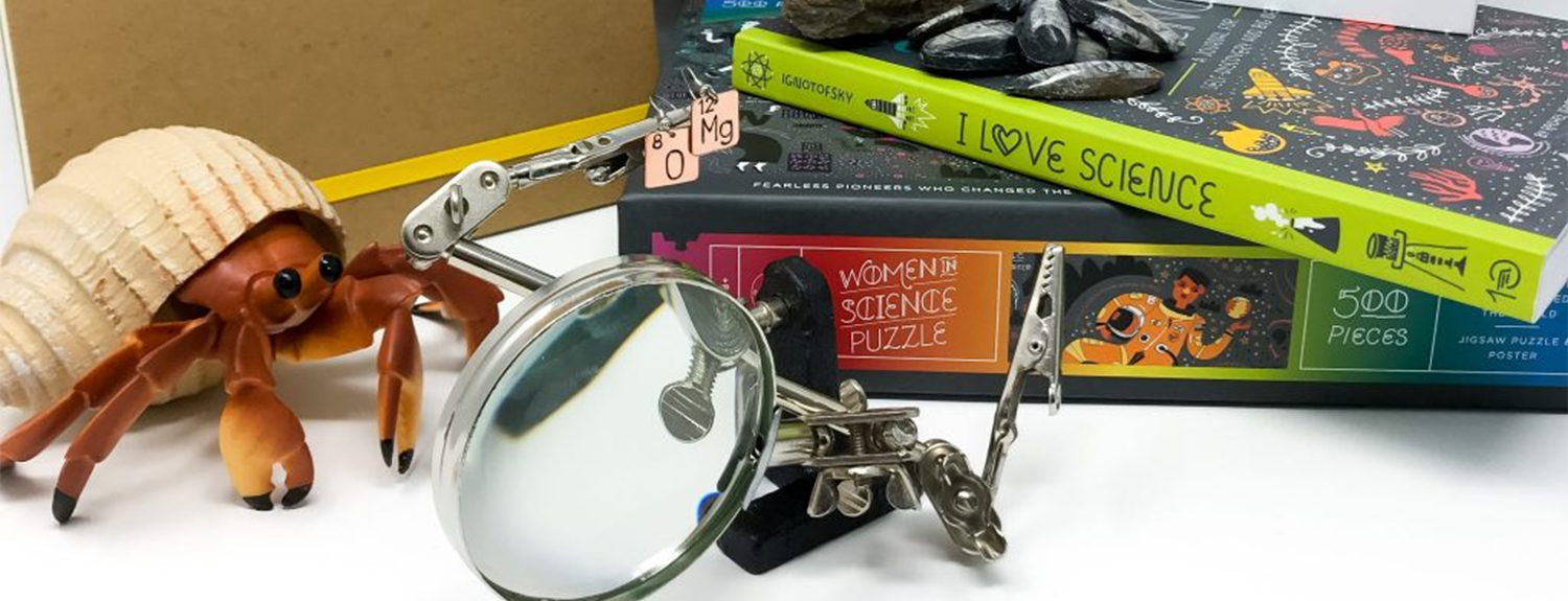 an assortment of quirky science gifts, including books and magnifying glass