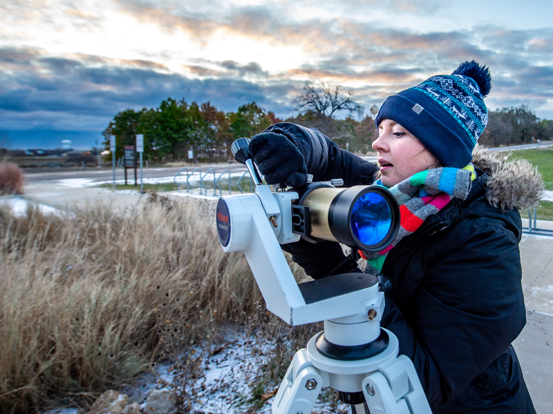 A planetarium educator looking through a telescope