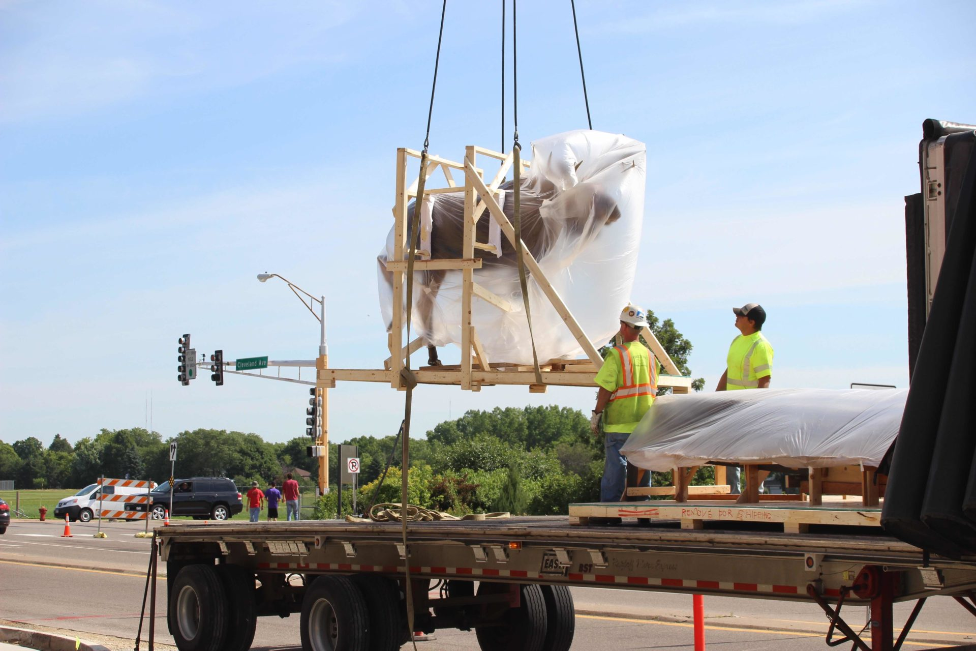 Taxidermy moose, wrapped in plastic, being lifted by crane