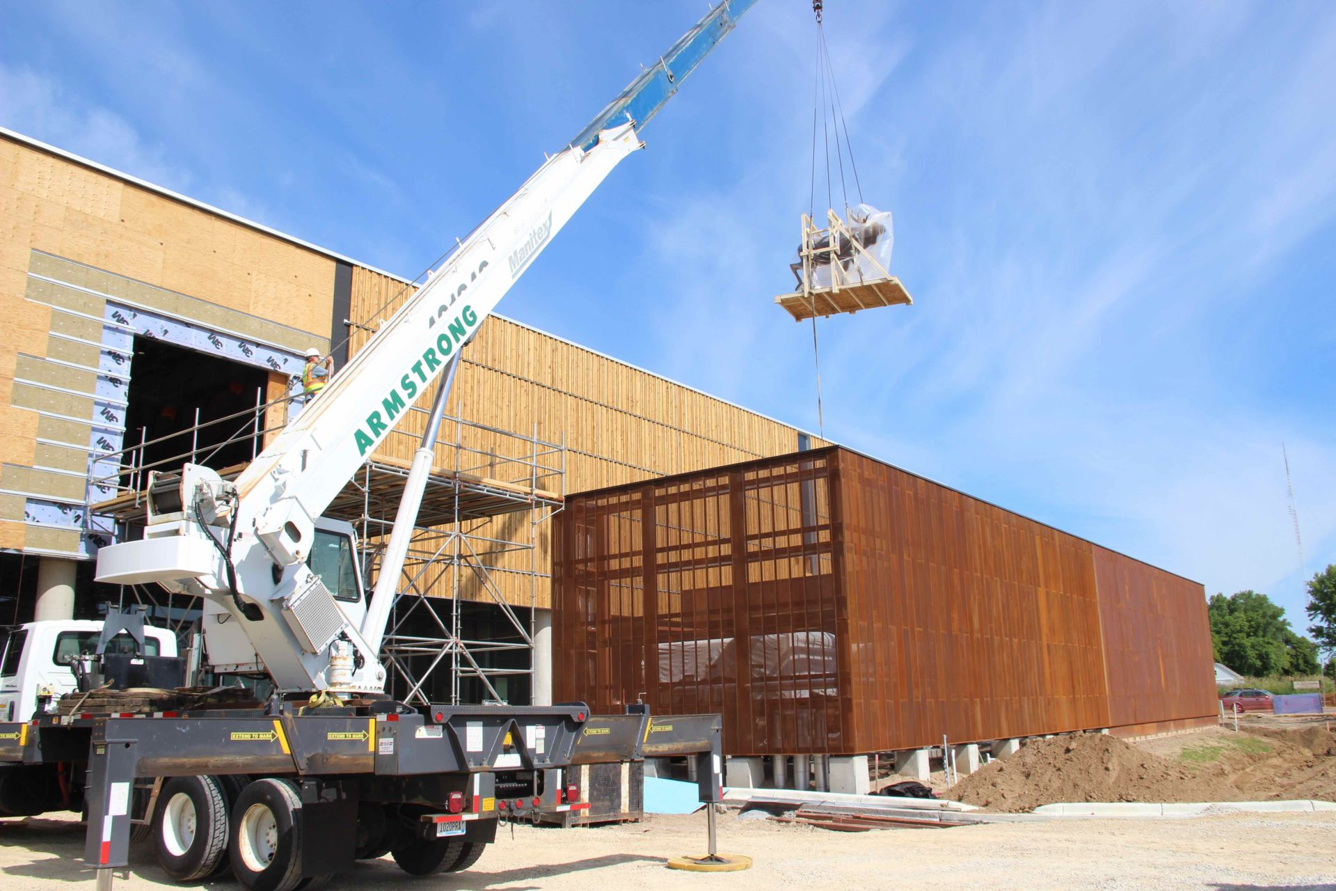 moose, wrapped in plastic, being lifted by a large crane into the new Bell Museum during construction