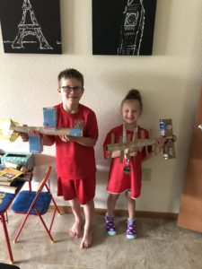2 children holding homemade models of space stations
