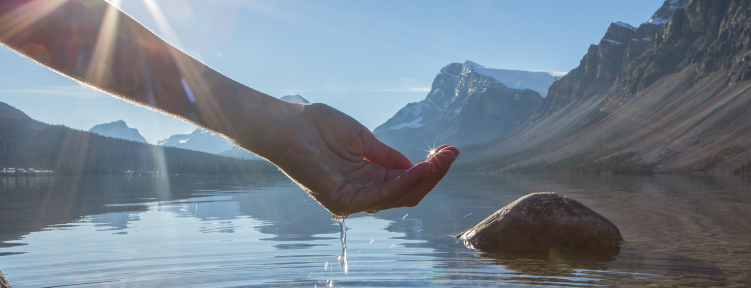 Hand holding a scoop of water in front of mountain lake