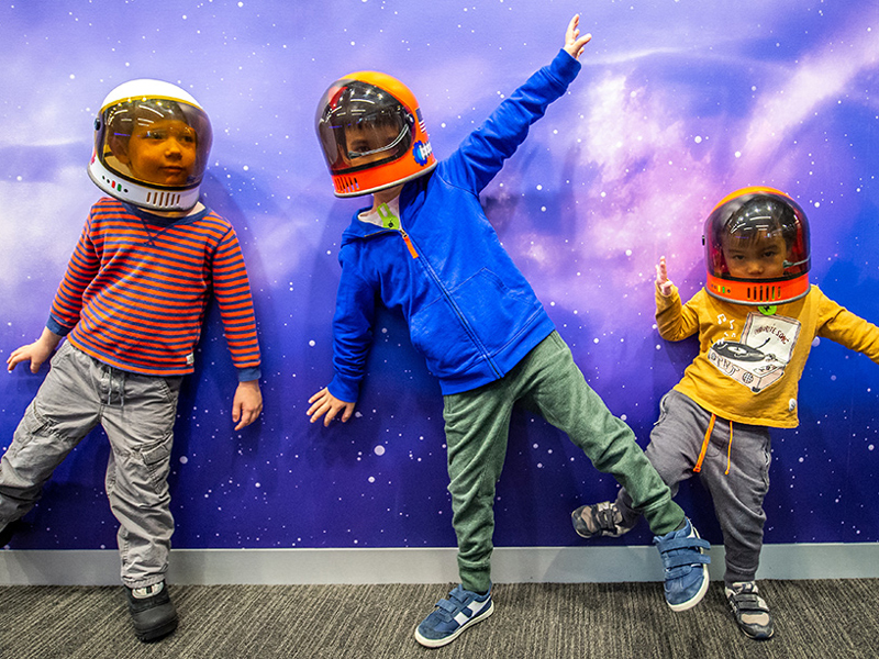 Kids in space helmets in front of the Bell's space wall