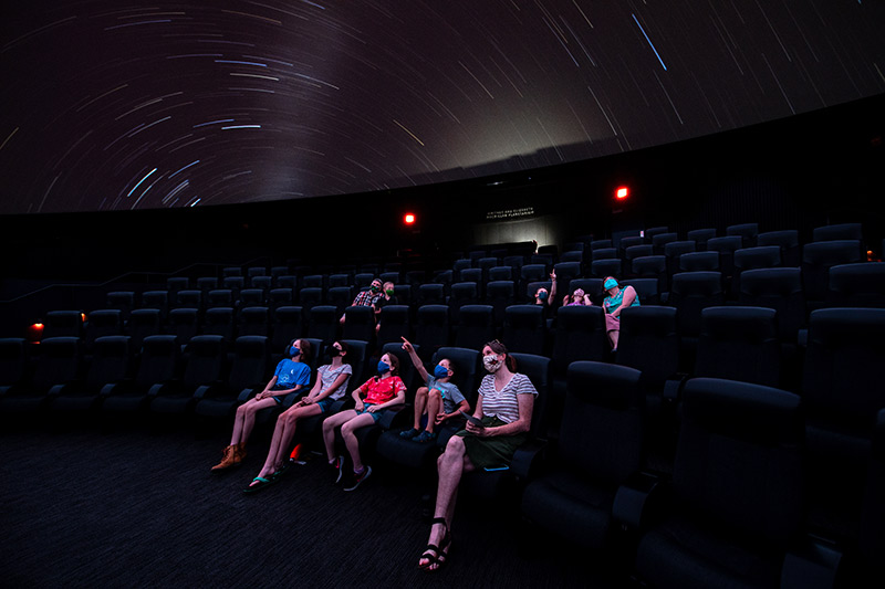 Audience in the planetarium wearing masks