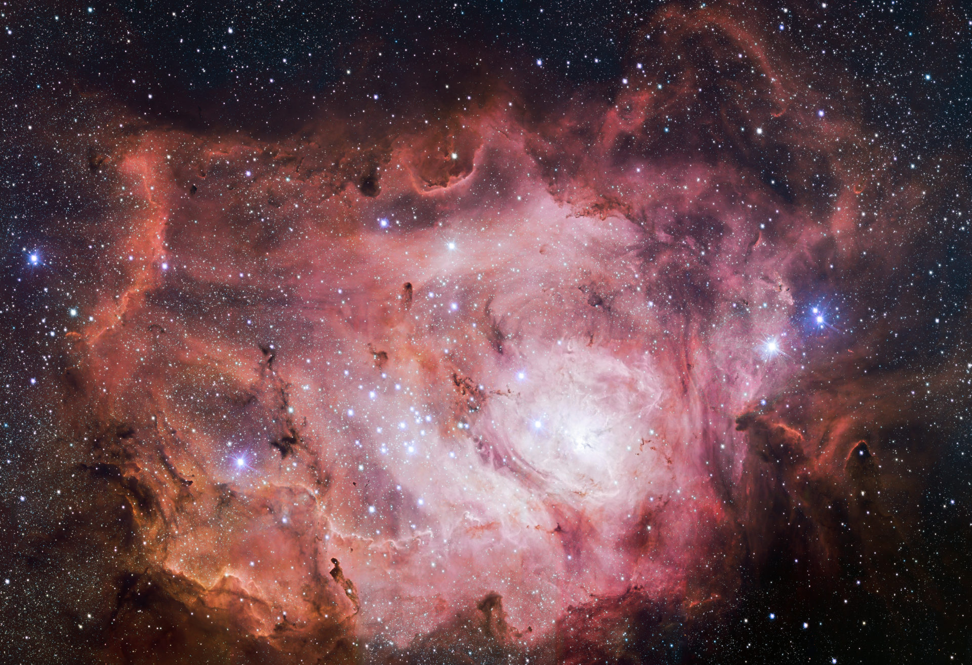A complex and mesmerizing pink nebula with wisps of red among the stars
