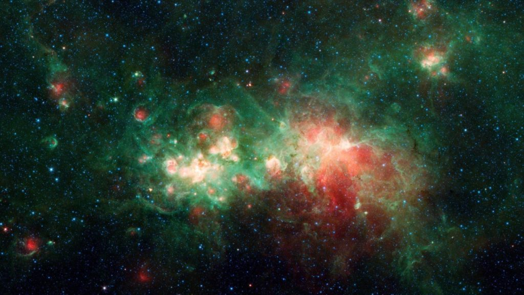spots of pink and green nebula in space