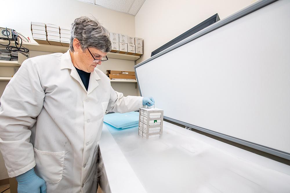 scientist in lab coat putting DNA samples into freezer