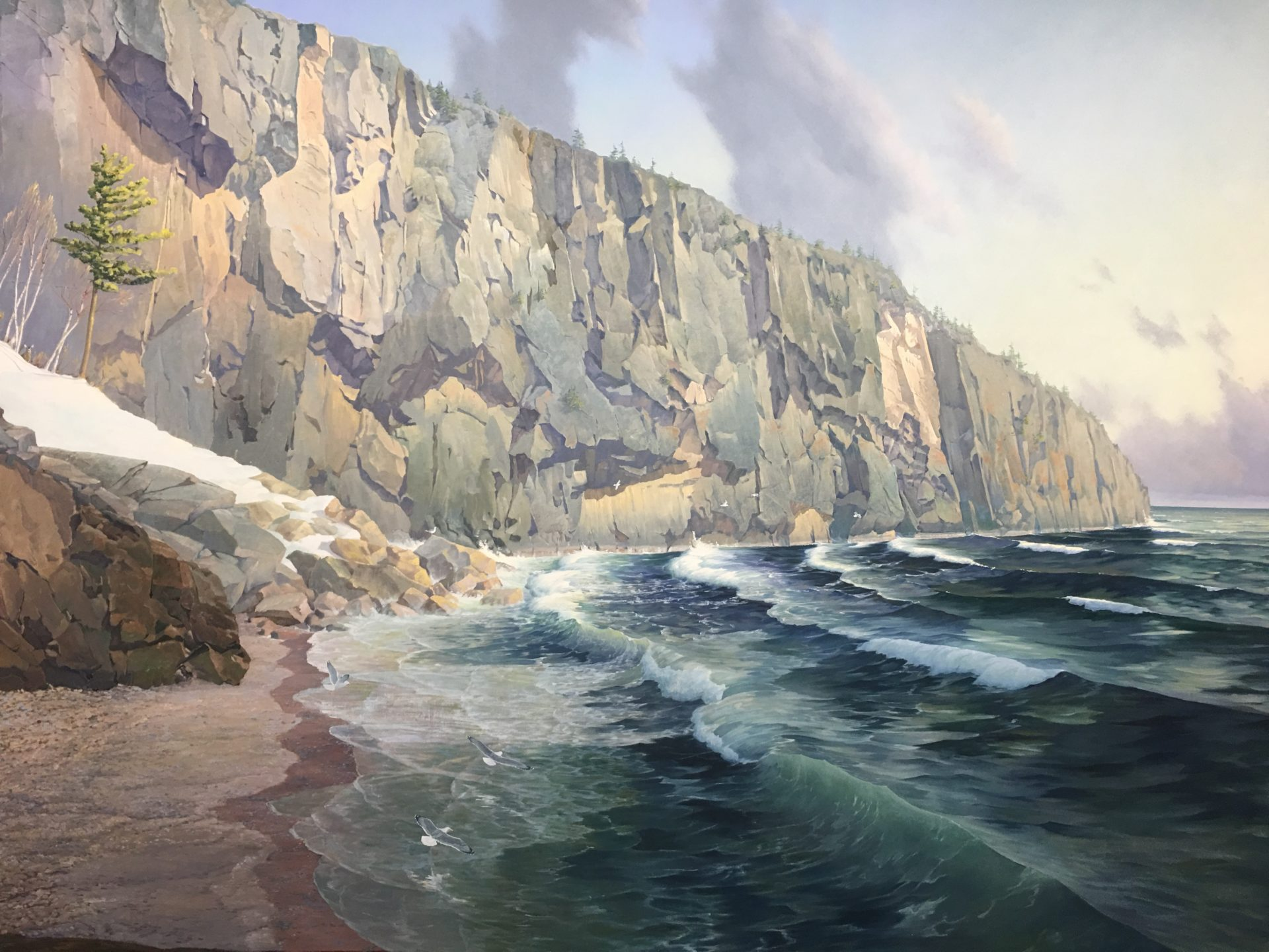 expansive shovel point painting, depicts cliffs and blue-green waves with white caps lapping onto the pebbly beach