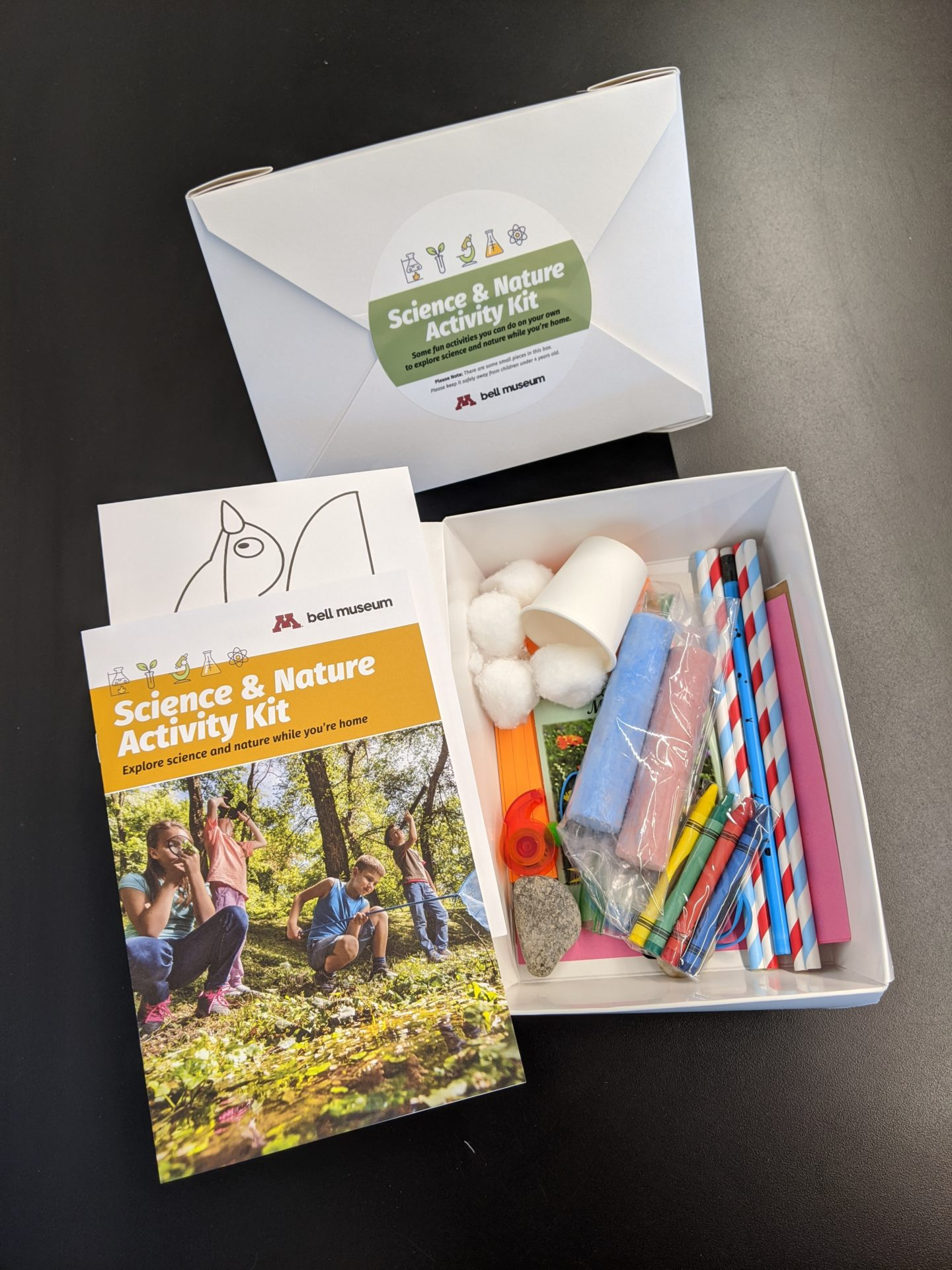 activity kits with guides and science and art contents such as chalk, pencils, cotton balls