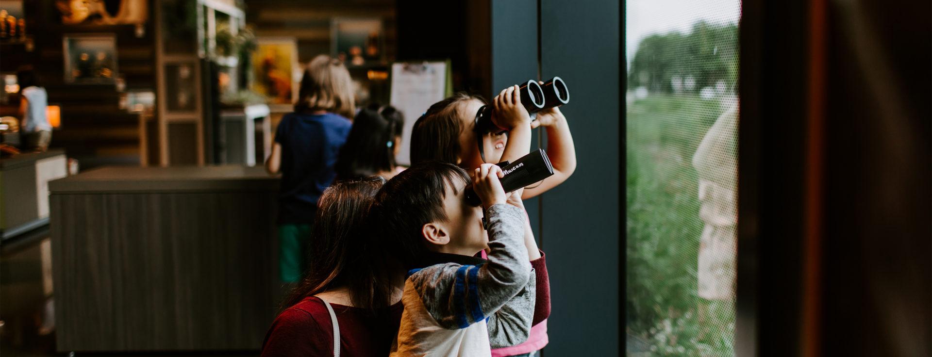 children look through binoculars out a window