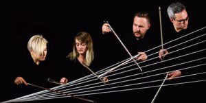 4 members of the Spektral Quartet playing on strings