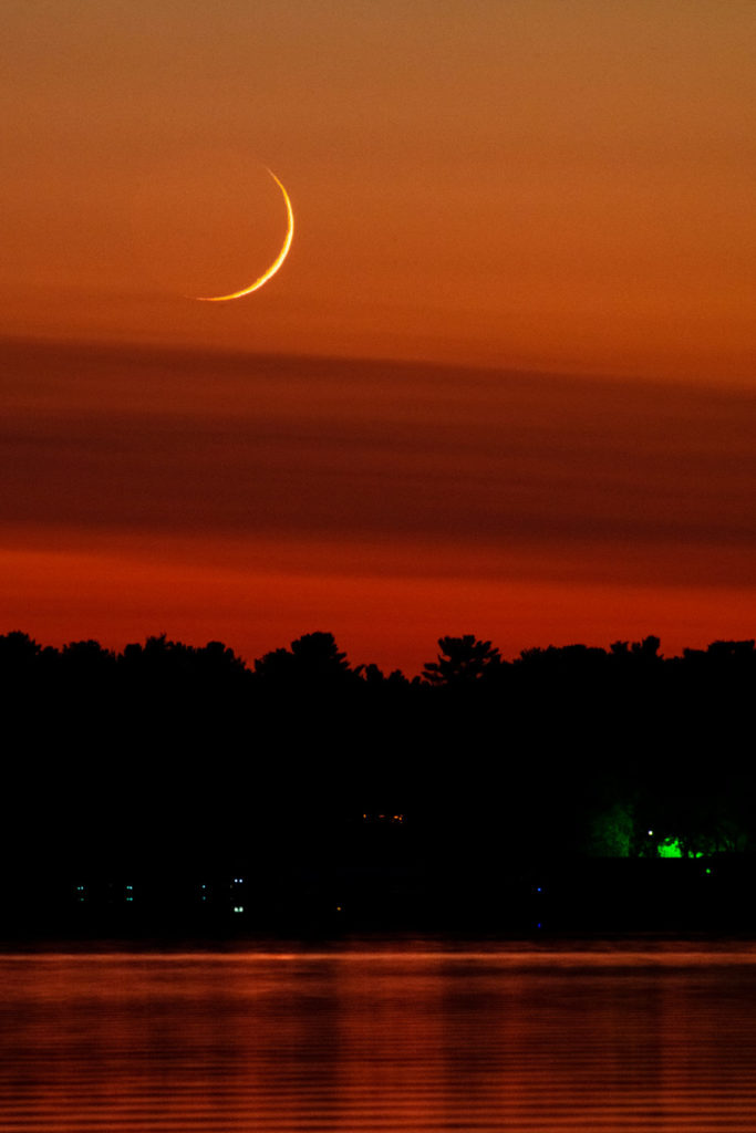 day and half old crescent moon over a lake