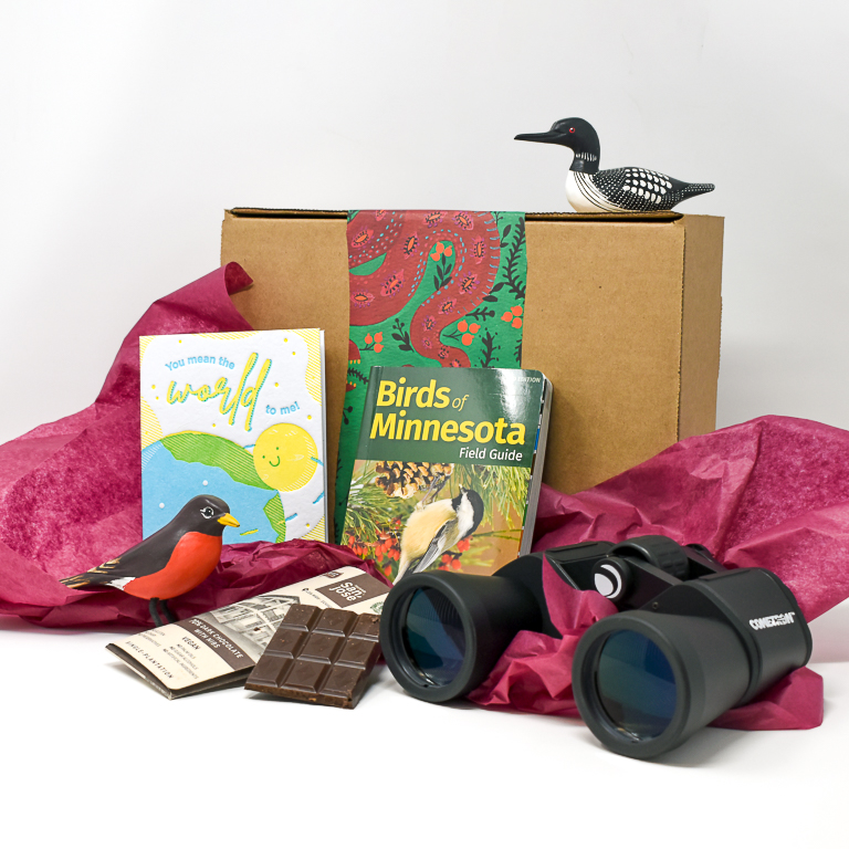Gift box with two wooden birds, a greeting card, binoculars and a chocolate bar